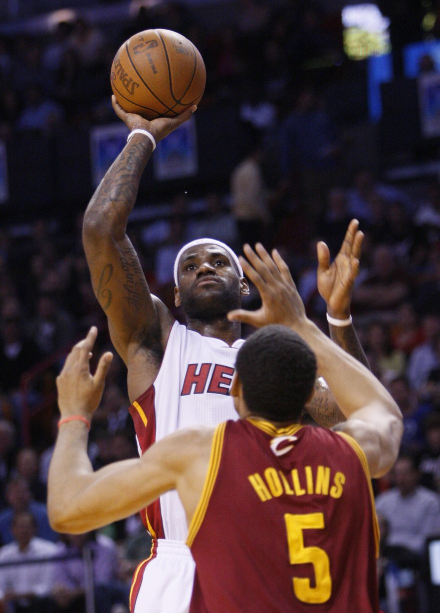 Miami Heat forward LeBron James, rear, goes up for a shot against Cleveland Cavaliers center Ryan Hollins (5) during the first half of an NBA basketball game Monday, Jan. 31, 2011 in Miami. (AP Photo/Wilfredo Lee)