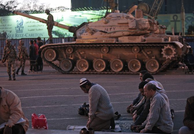 Anti-government protesters offer their evening prayers Monday in front of an Egyptian army tank securing the area during a protest in Cairo's Tahrir Square. A coalition of opposition groups called for a million people to take to Cairo's streets Tuesday to demand the removal of Egyptian President Hosni Mubarak. (Associated Press)
