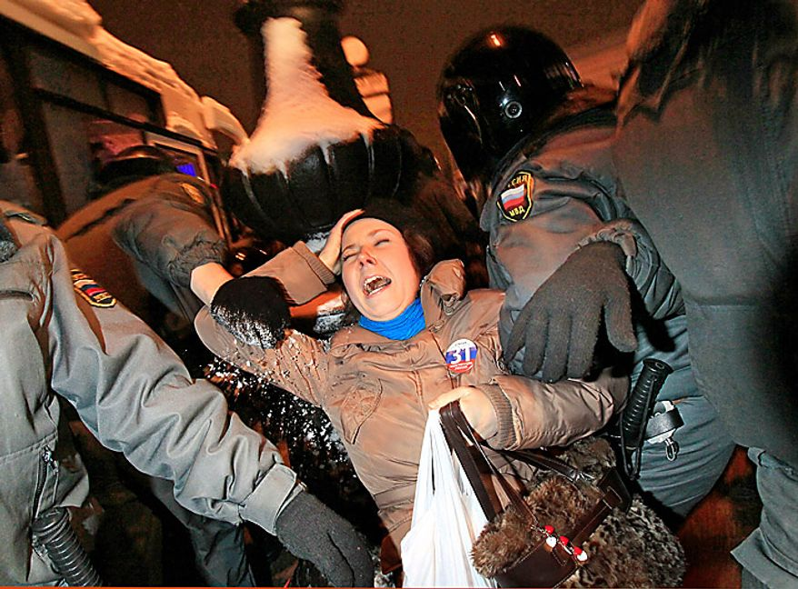 Police officers detain an opposition activist during a banned anti-Kremlin protest in St. Petersburg, Russia, Monday, Jan. 31, 2011.  Opposition groups have been calling rallies on the 31st day of each month to honor Article 31 of the Russian Constitution, which guarantees the right of assembly. Most of the rallies have been banned or dispersed by police as unsanctioned. (AP Photo/Dmitry Lovetsky)