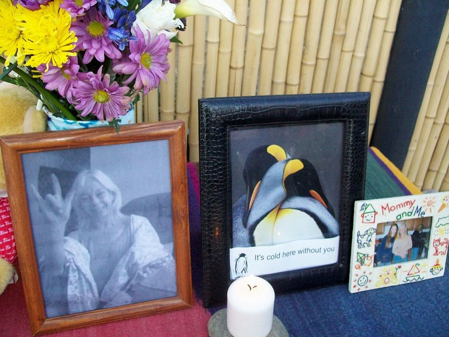 Photographs, flowers and other tributes arranged by Mrs. Ellis' family are set out at the site of her outdoor cremation. (Associated Press)