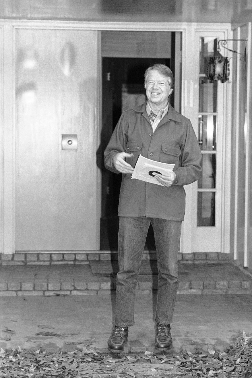 President Jimmy Carter talks briefly with members of the press at the front door of his Plains, Ga., home Saturday, Dec. 24, 1977 after talking with farm strike representatives. (AP Photo/DC)