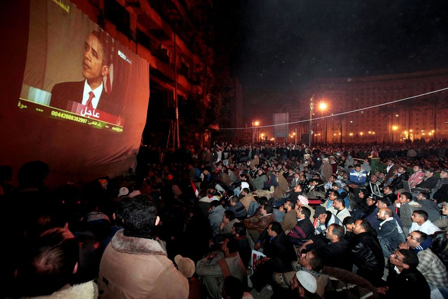 Anti-government demonstrators, gathered in Cairo's Tahrir Square early Wednesday, watch President Obama live in Washington as he speaks about the crisis in Egypt and lauds Mr. Mubarak's decision not to seek re-election. (Associated Press)