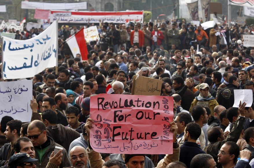 Demonstrators hold banners in Tahrir, or Liberation, Square in Cairo on Tuesday, Feb. 1, 2011, to demand that President Hosni Mubarak step down after nearly 30 years in power. (AP Photo/Khalil Hamra)