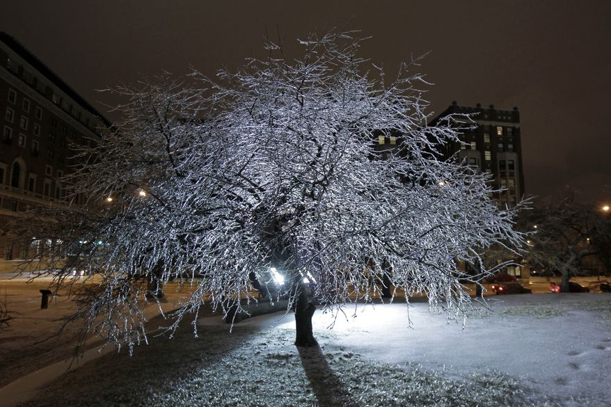 An ice-covered tree glistens from spotlights on the grounds of the Indiana War Memorial in downtown Indianapolis on Monday, Jan. 31, 2011. (AP Photo/Michael Conroy)