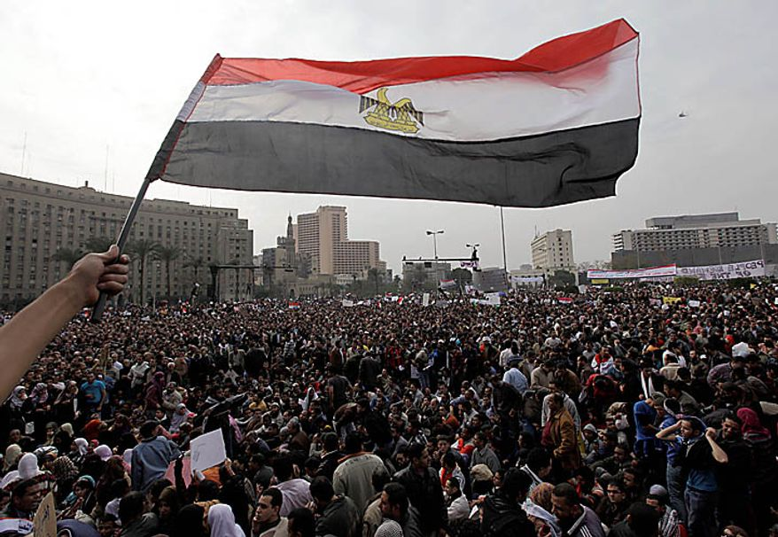 A demonstrator waves an Egyptian flag as the crowd gathers in Tahrir, or Liberation, Square in Cairo on Tuesday, Feb. 1, 2011. More than a quarter-million people flooded into the heart of Cairo, filling the city's main square in by far the largest demonstration in a week of unceasing demands for President Hosni Mubarak to leave after nearly 30 years in power. (AP Photo/Ben Curtis)