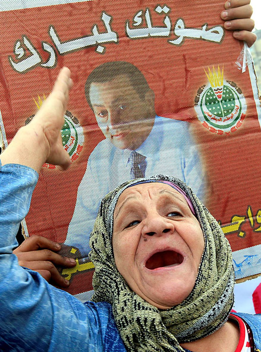 """An elderly Egyptian pro-Mubarak supporter shouts slogans during a demonstration in Cairo on Tuesday, Feb. 1, 2011. Egyptian authorities battled to save President Hosni Mubarak's regime with a series of concessions and promises to protesters, but realities on the streets of Cairo may be outrunning his capacity for change. The Arabic poster, dating from the 2005 presidential elections, reads, """"Your vote to Mubarak."""" (AP Photo/Amr Nabil)"""