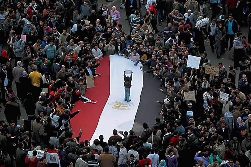 An Egyptian boy stands on an Egyptian flag as anti-government protesters crowd around in Tahrir, or Liberation, Square in Cairo on Tuesday, Feb. 1, 2011. More than a quarter-million people flooded into the heart of Cairo, filling the city's main square in by far the largest demonstration in a week of unceasing demands for President Hosni Mubarak to leave after nearly 30 years in power. (AP Photo/Tara Todras-Whitehill)
