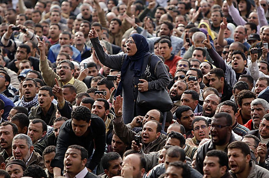 A demonstrator reacts in Tahrir, or Liberation, Square in Cairo on Tuesday, Feb. 1, 2011. More than a quarter-million people flooded into the heart of Cairo, filling the city's main square in by far the largest demonstration in a week of unceasing demands for President Hosni Mubarak to leave after nearly 30 years in power. (AP Photo/Ben Curtis)