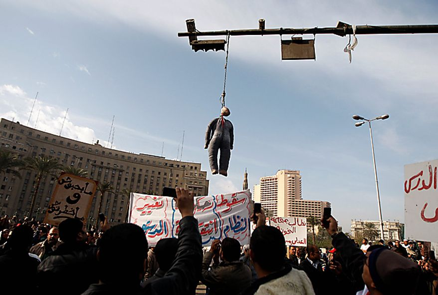 An effigy of Egyptian President Hosni Mubarak hangs while people demonstrate in Tahrir, or Liberation, Square in Cairo on Tuesday, Feb. 1, 2011. Security officials say authorities shut down all roads and public transportation to Cairo, where tens of thousands of people converged to demand the ouster of Mr. Mubarak after nearly 30 years in power. (AP Photo/Khalil Hamra)