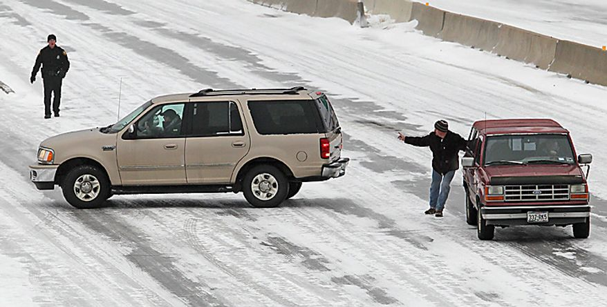 A Fort Worth, Texas, police officer (left) and a motorist try to help stranded and spun-out motorists on Interstate 30 eastbound at Green Oaks in Fort Worth. A severe winter storm hit North Texas with freezing rain, ice and snow. (AP Photo/Fort Worth Star-Telegram, Paul Moseley)