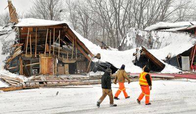 Officials check out the Worcester Winnelson Co., building that collapsed in Auburn, Mass., on Wednesday after heavy snow followed by rain. (Associated Press)
