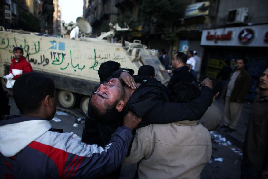 An injured anti-government protester is carried past an army vehicle during clashes Wednesday in Tahrir Square in Cairo. Protesters continue to call for President Hosni Mubarak's immediate ouster. (Associated Press)