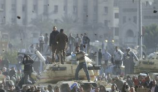 Stones fly through the air as supporters of President Hosni Mubarak, foreground, fight with anti-Mubarak protesters, rear, standing on army tanks in Cairo, Egypt, Wednesday, Feb.2, 2011. Several thousand supporters of Mr. Mubarak, including some riding horses and camels and wielding whips, clashed with anti-government protesters Wednesday as Egypt's upheaval took a dangerous new turn. (AP Photo/Ahmed Ali)