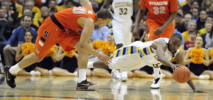 Syracuse's Brandon Triche (20) and Marquette's Junior Cadougan (5) dive for a loose ball during the second half of an NCAA college basketball game Saturday, Jan. 29, 2011, in Milwaukee. (AP Photo/Jim Prisching)