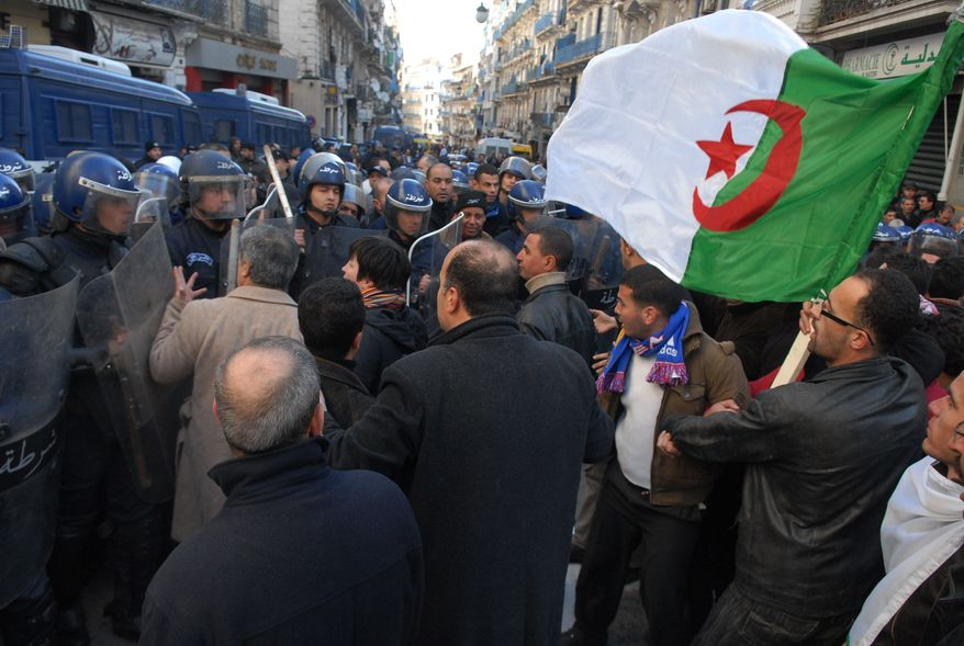 ** FILE ** Protesters carrying an Algerian flag face riot policemen In Algiers on Saturday, Jan. 22, 2011, during a demonstration against a ban on public gatherings. (AP Photo)