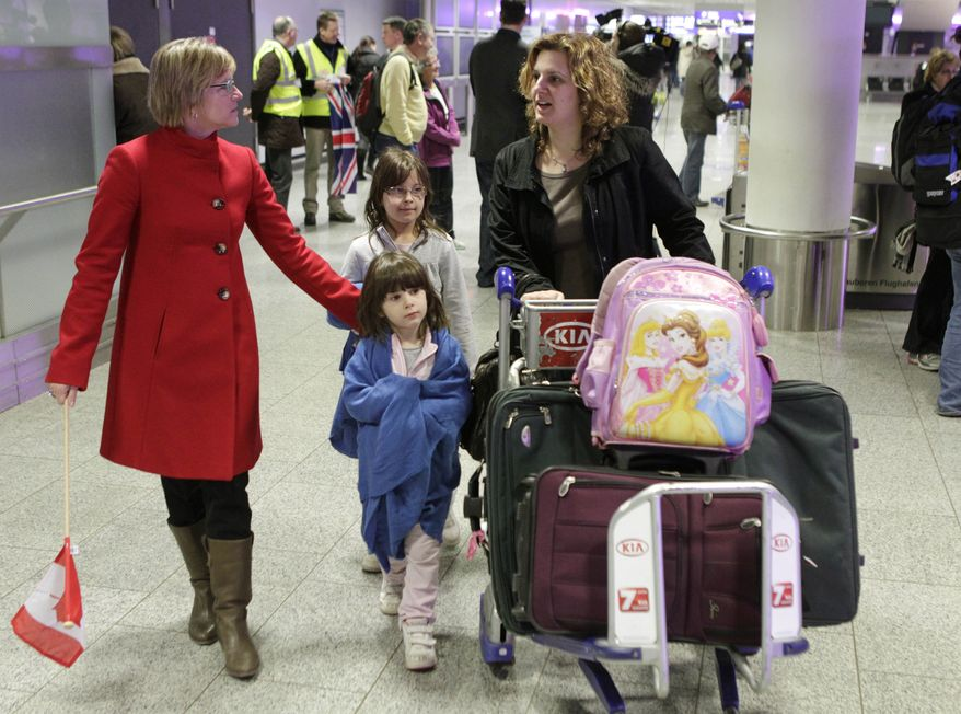 A Canadian mother and her two children are welcomed by an employee of the Canadian Embassy at Frankfurt Airport in Germany on Tuesday, Feb. 1, 2011, after they were flown out of Cairo by Air Canada. (AP Photo/Michael Probst)
