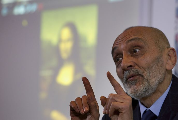 """Art historian Silvano Vinceti gestures as a photo of Italian artist Leonardo da Vinci's """"Mona Lisa"""" painting is projected in the background during a press conference in Rome on Wednesday, Feb. 2, 2011. Mr. Vinceti said the main influence and model for the """"Mona Lisa"""" was a male apprentice of Leonardo da Vinci, Gian Giacomo Caprotti, known as Salai, who worked with Leonardo for years starting in 1490. (AP Photo/Andrew Medichini)"""