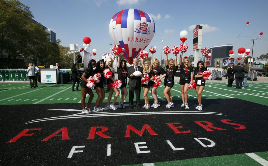 Paul Palsu, Farmers Insurance president, center, poses with Los Angeles Kings cheerleaders, Tuesday, Feb. 1, 2011, during a ceremony naming a new NFL stadium in Los Angeles. A proposed NFL stadium in downtown Los Angeles would be called Farmers Field under a 30-year naming-rights deal between developer AEG and Farmers Insurance Exchange. (AP Photo/Nick Ut)