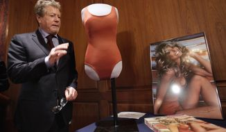 Actor Ryan O'Neal waves goodbye to Farrah Fawcett's red swimsuit, and seen in a poster at right, and other Fawcett memorabilia, at the Smithsonian's National Museum of American History, in Washington, Wednesday, Feb. 2, 2011, where he donated objects from the private collection of Farrah Fawcett's estate. (AP Photo/Jacquelyn Martin)