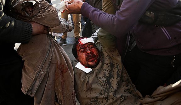 An injured anti-government protester is carried away from clashes in Tahrir, or Liberation, Square, in Cairo, Egypt, Wednesday, Feb. 2, 2011. Several thousand supporters of President Hosni Mubarak, including some riding horses and camels and wielding whips, clashed with anti-government protesters Wednesday as Egypt's upheaval took a dangerous new turn. (AP Photo/Tara Todras-Whitehill)