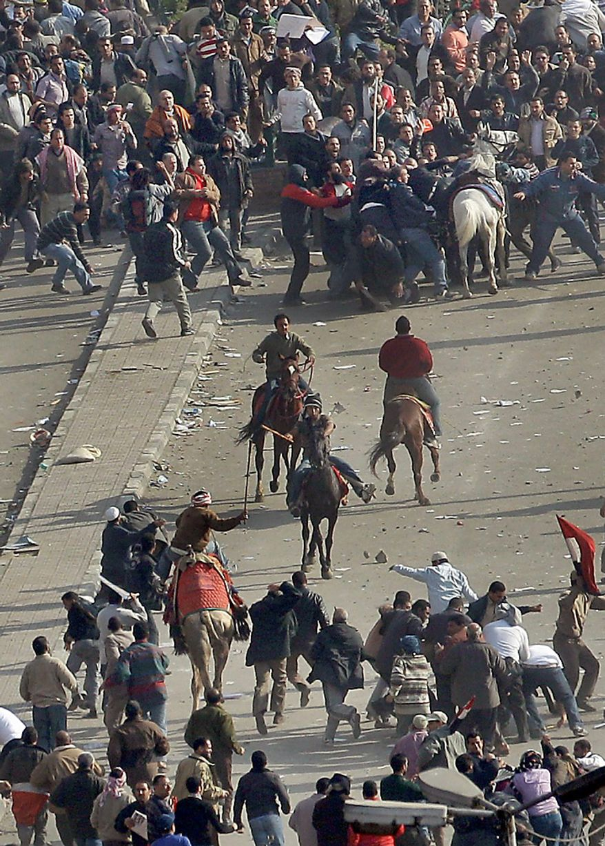 Pro-government demonstrators, below, some riding camels and horses and armed with sticks, clash with anti-government demonstrators, above, who pull one off his white horse and beat him, in Tahrir square, the center of anti-government demonstrations, in Cairo, Egypt, Wednesday, Feb. 2, 2011. (AP Photo/Ben Curtis)