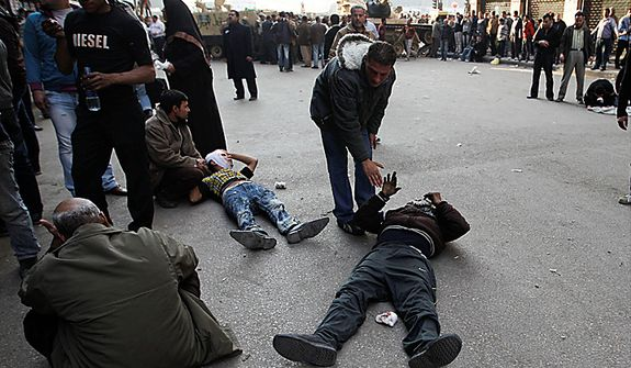 Injured anti-government protesters lie on the ground near army vehicles as they wait to be treated by medics during clashes in Tahrir, or Liberation, Square, in Cairo, Egypt, Wednesday, Feb. 2, 2011. Several thousand supporters of President Hosni Mubarak, including some riding horses and camels and wielding whips, clashed with anti-government protesters Wednesday as Egypt's upheaval took a dangerous new turn. (AP Photo/Tara Todras-Whitehill)