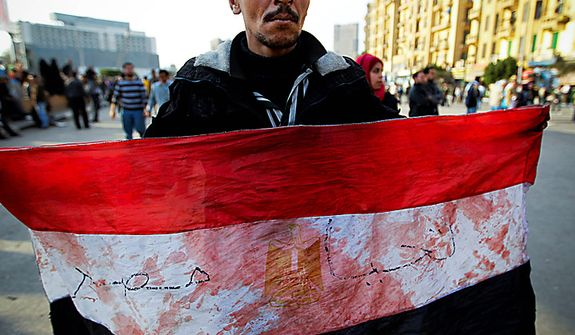 An anti-government protester displays an Egyptian flag, covered with blood, during clashes in Tahrir, or Liberation, Square, in Cairo, Egypt, Wednesday, Feb. 2, 2011. Several thousand supporters of President Hosni Mubarak, including some riding horses and camels and wielding whips, clashed with anti-government protesters Wednesday as Egypt's upheaval took a dangerous new turn. (AP Photo/Tara Todras-Whitehill)