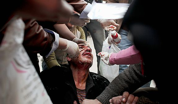 An injured anti-government protester sits on the ground as he is treated by medics during clashes in Tahrir, or Liberation, Square, in Cairo, Egypt, Wednesday, Feb. 2, 2011. Several thousand supporters of President Hosni Mubarak, including some riding horses and camels and wielding whips, clashed with anti-government protesters as Egypt's upheaval took a dangerous new turn. (AP Photo/Tara Todras-Whitehill)