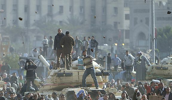 Stones fly through the air as supporters of President Hosni Mubarak, foreground , fight with anti-Mubarak protesters, rear, standing on army tanks in Cairo, Egypt, Wednesday, Feb.2, 2011. Several thousand supporters of  Mr. Mubarak, including some riding horses and camels and wielding whips, clashed with anti-government protesters Wednesday as Egypt's upheaval took a dangerous new turn. (AP Photo/Ahmed Ali)