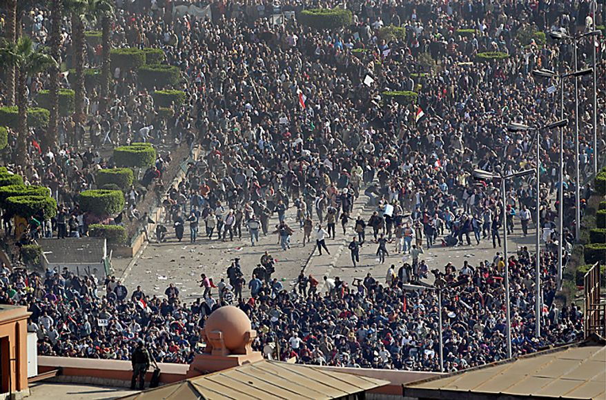 Pro-government demonstrators, below, clash with anti-government demonstrators, above, as an Egyptian Army soldier on the rooftop of the Egyptian Museum observes the scene in Tahrir Square, the center of anti-government demonstrations, in Cairo, Egypt, Wednesday, Feb. 2, 2011. (AP Photo/Ben Curtis)