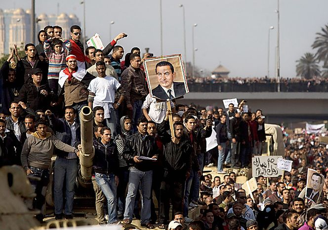 Pro-government demonstrators show their support for Egyptian President Hosni Mubarak during a demonstration in Cairo on Wednesday, Feb. 2, 2011. Several thousand Mubarak supporters, including some riding horses and camels and wielding whips, clashed with anti-government protesters as Egypt's upheaval took a dangerous new turn. In chaotic scenes, the two sides pelted each other with stones, and protesters dragged riders off their horses. (AP Photo/Sebastian Scheiner)