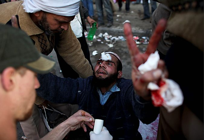 An injured anti-government protester gestures as he is treated by medics during clashes in Tahrir, or Liberation, Square, in Cairo, Egypt, Wednesday, Feb. 2, 2011. Several thousand supporters of President Hosni Mubarak clashed with anti-government protesters as Egypt's upheaval took a dangerous new turn. (AP Photo/Tara Todras-Whitehill)