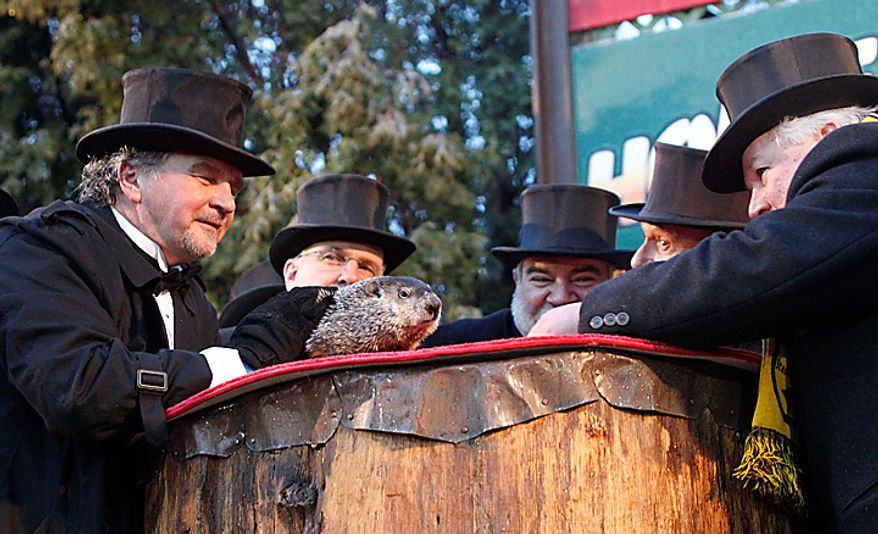 Groundhog Club President Bill Deeley (right) looks at and listens to Punxsutawney Phil, the weather-predicting groundhog, as handler John Griffiths (left) awaits Phil's prognostication on Groundhog Day, Wednesday, Feb. 2, 2011, in Punxsutawney, Pa. (AP Photo/Keith Srakocic)