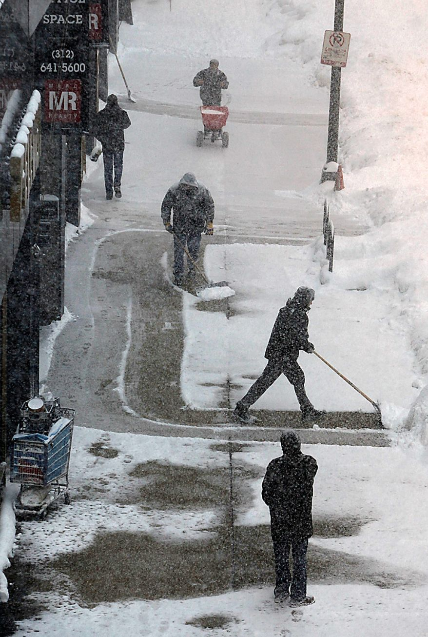 Workers clear the sidewalk during a blizzard Wednesday, Feb. 2, 2011, in Chicago. Forecasts call for snow accumulation between one and two feet. (AP Photo/Charles Rex Arbogast)