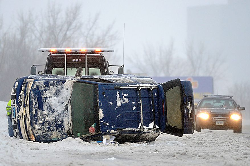 An SUV lies on its side after a rollover in sleeting conditions in Hartford, Conn., Wednesday, Feb. 2, 2011.  (AP Photo/Jessica Hill)