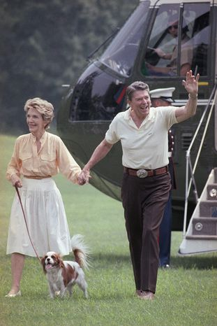 President Reagan and first lady Nancy Reagan, with their dog Rex, wave to White House visitors on July 27, 1986. (Associated Press)