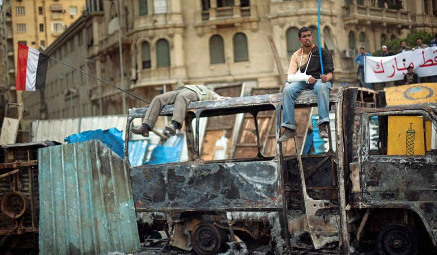 """BURNED OUT: The remains of a vehicle in Cairo is a temporary resting place for anti-government protesters on Thursday. Looting, arson and beatings have become the norm in demonstrations that started peacefully last week, but activists still hope for a massive turnout on """"Departure Friday."""" (Associated Press)"""