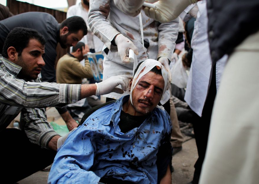 Egyptian doctors and medics treat an injured suspected government supporter near Tahrir Square in Cairo on Thursday. (Associated Press)