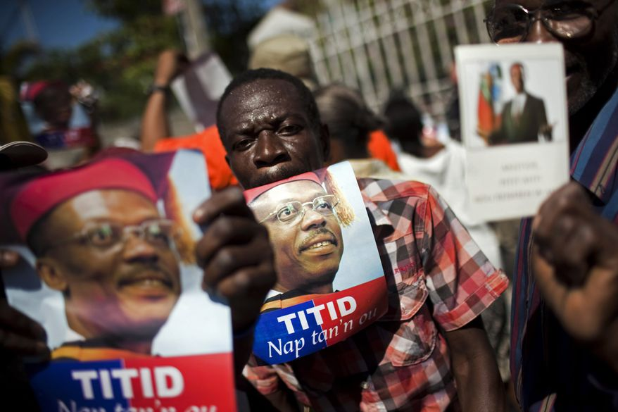 Demonstrators hold pictures of Haiti's ousted President Jean Bertrand Aristide during a protest demanding his return in Port-au-Prince, Haiti, Wednesday Feb. 2, 2011. (AP Photo/Rodrigo Abd)