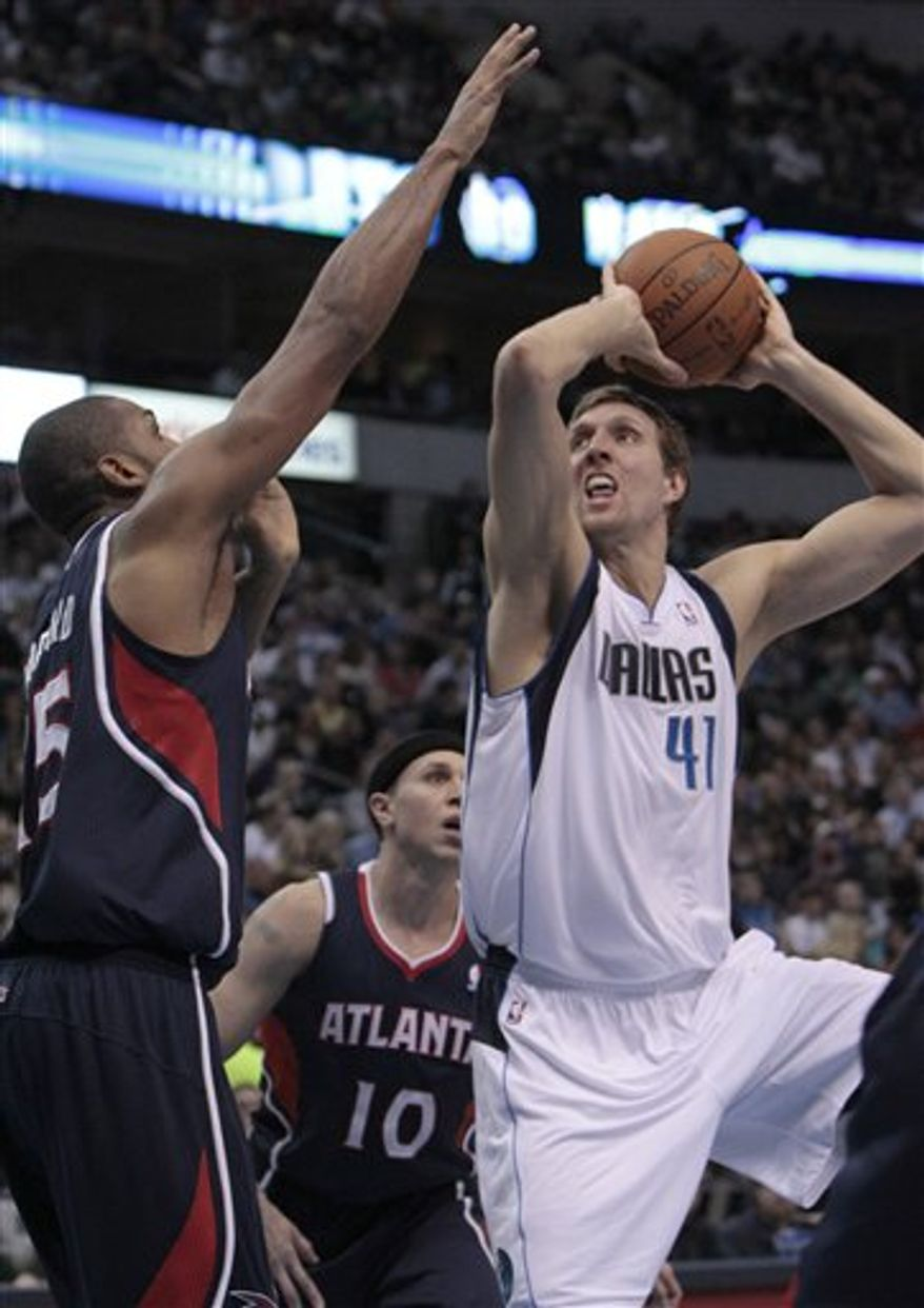 Dallas Mavericks' Dirk Nowitzki (41) of Germany shoots against Atlanta Hawks' Jordan Crawford (55) as Mike Bibby (10) looks on  during the first half of their NBA basketball game in Dallas,  Saturday, Jan. 29, 2011.   (AP Photo/LM Otero)