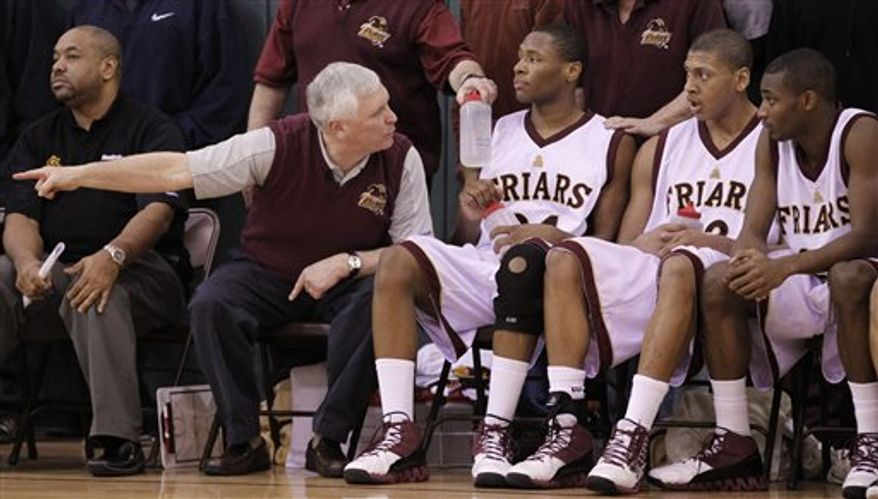 ** FILE ** Bob Hurley (second from left), head coach of the St. Anthony High School boys basketball team, huddles with his players during a game against St. Mary's on Wednesday, Feb. 2, 2011, in Jersey City, N.J. St. Anthony won the game 76-46, giving Hurley his 1,000 career coaching victory. (AP Photo/Julio Cortez)