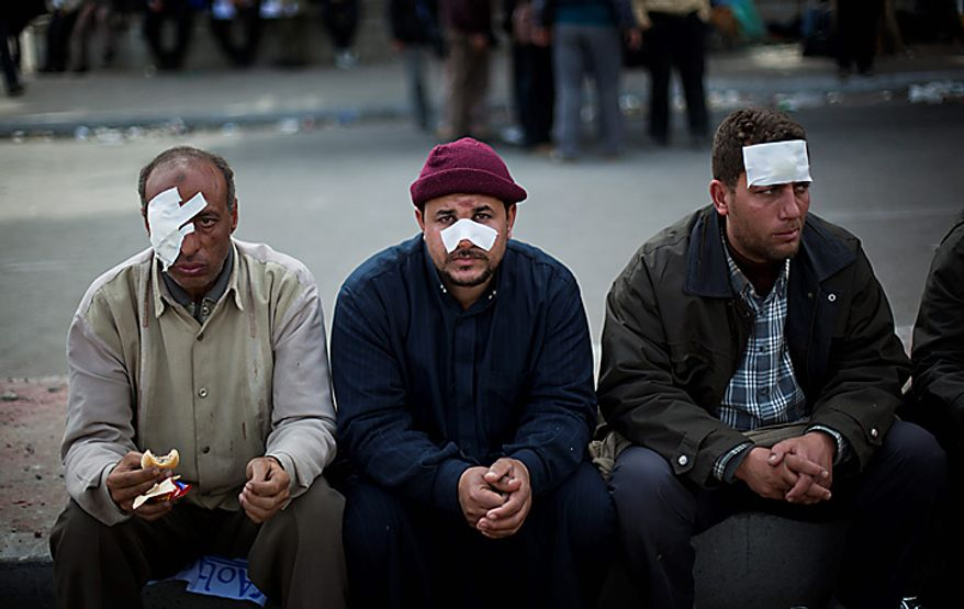 Wounded Egyptian anti-government protesters sit in Cairo's main square Thursday, Feb. 3, 2011. New clashes are heating up and shots are being fired in the air around Cairo's central Tahrir Square as anti-government protesters push back regime supporters and two sides are trading volleys of stone-throwing. (AP Photo/Emilio Morenatti)