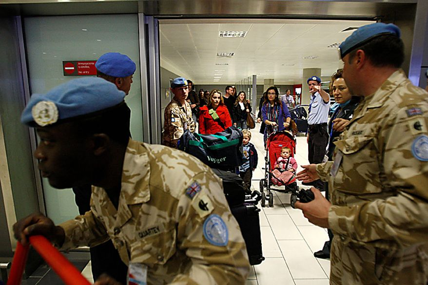 U.N. soldiers escort U.N. staff based in Egypt after they arrive in Cyprus' Larnaca airport, Thursday, Feb. 3 2011. The United Nations is evacuating its 350 Egypt-based staff members to the east Mediterranean island due to security concerns. Around 150 U.N. staff and their dependents arrived aboard a U.N. chartered flight from Cairo on Thursday. (AP Photo/Petros Karadjias)