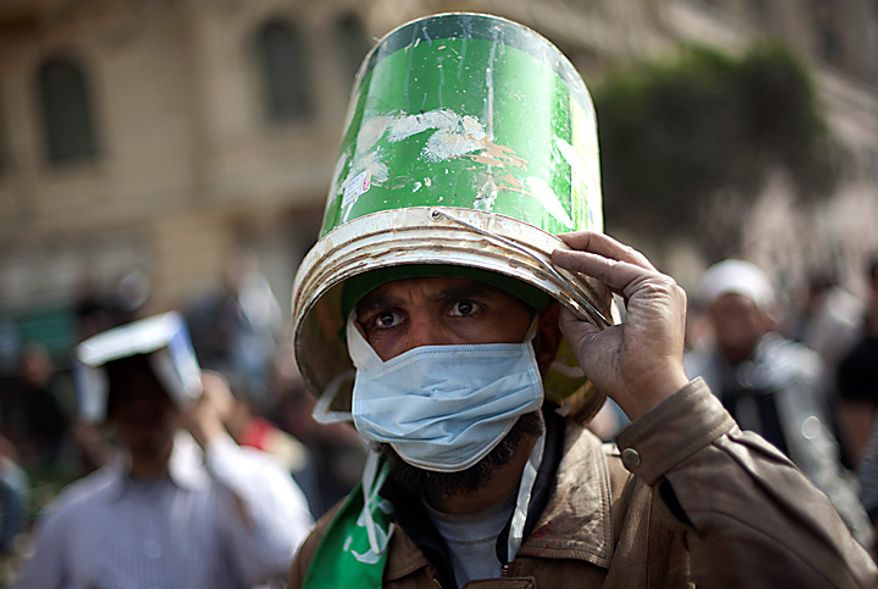 An Egyptian anti-government protester uses a bucket as a helmet during clashes in Cairo's Tahrir Square Thursday, Feb. 3, 2011. Protesters and regime supporters skirmished in a second day of rock-throwing battles at a central Cairo square while new lawlessness spread around the city. (AP Photo/Emilio Morenatti)