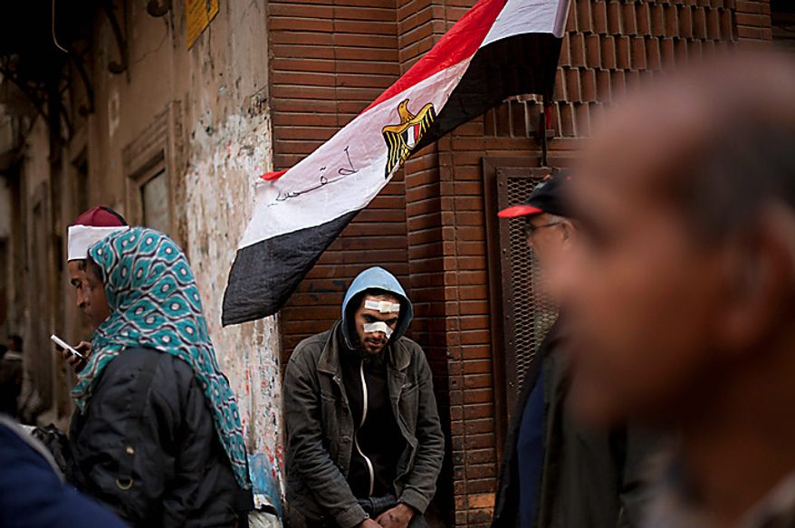 A wounded Egyptian anti-government protester rests during clashes in Cairo's main square Thursday, Feb. 3, 2011. Another bout of heavy gunfire and clashes erupted Thursday around dusk in the Cairo square at the center of Egypt's anti-government chaos, while new looting and arson spread around the capital. (AP Photo/Emilio Morenatti)