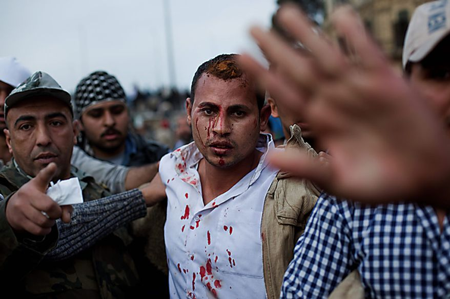 A man suspected of being a plain-clothed policeman is escorted by anti-government protesters during clashes in Cairo, Egypt, Thursday, Feb. 3, 2011. Egypt's prime minister apologized for an attack by government supporters on protesters in a surprising show of contrition Thursday, and the government offered more concessions to try to calm the wave of demonstrations demanding the ouster of President Hosni Mubarak. (AP Photo/Emilio Morenatti)