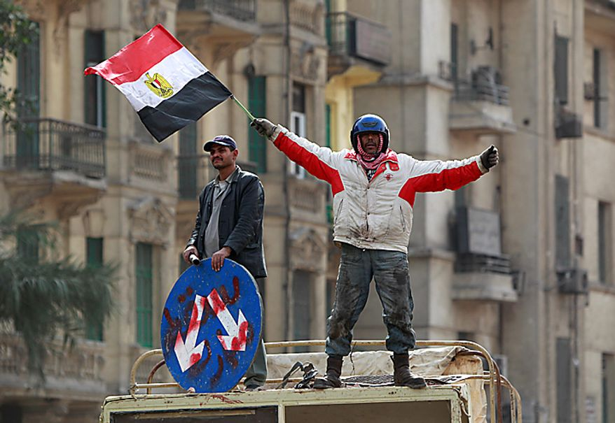 An anti-government protester waves the national flag in Cairo's main square Thursday, Feb. 3, 2011. Egyptian army tanks and soldiers moved to end violence between anti-government protesters and supporters of President Hosni Mubarak in Cairo's central square on Thursday after standing by for nearly a day as the two sides battled with rocks, sticks, bottles and firebombs. (AP Photo/Ben Curtis)