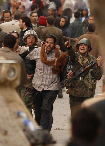 Anti-government demonstrators hand over to the the army a man, center, they suspect to be a supporter of Egyptian President Hosni Mubarak in Cairo's Tahrir Square Thursday, Feb. 3, 2011. (AP Photo/Victoria Hazou)