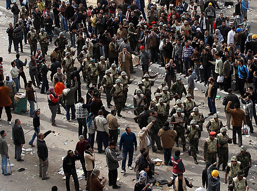 Egyptian army soldiers patrol through anti- government protesters in downtown Cairo Thursday, Feb. 3, 2011.  (AP Photo/Khalil Hamra)