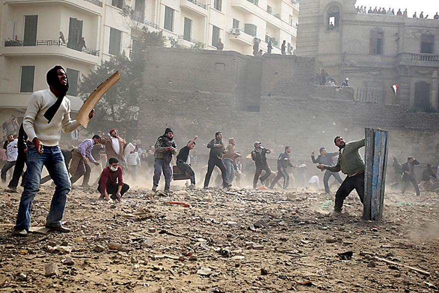Egyptian anti-government protesters throw stones during clashes in downtown Cairo Thursday, Feb. 3, 2011. (AP Photo/Khalil Hamra)